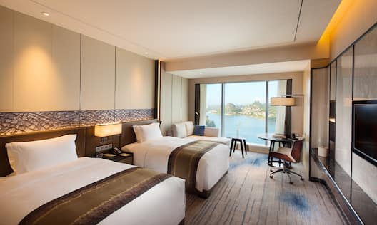 Two Twin Beds, Illuminated Lamp Above Bedside Table, Sofa by Large Window With Lake View, Work Desk and TV