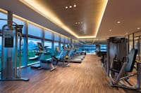 Fitness Center With Cardio Equipment by Large Window With Mountain View