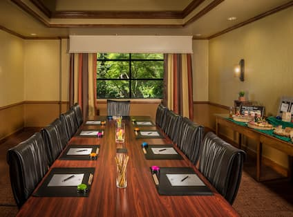 Window With Open Drapes, Food Service Area, and Seating for 9 Around Table in Exeter Boardroom