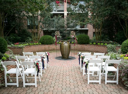White Chairs Decorated with Flowers for and an Event on Outdoor Patio
