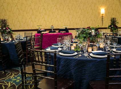 Place Settings and Flowers on Round Table With Blue Cloths, Chairs and Food Service Table With Red Cloth in Banquet Room