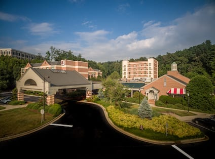 Aerial View of Hotel Exterior, Signage, Landscaping, Porte Cochere and Guest Cars on Parking Lot on a Sunny Day
