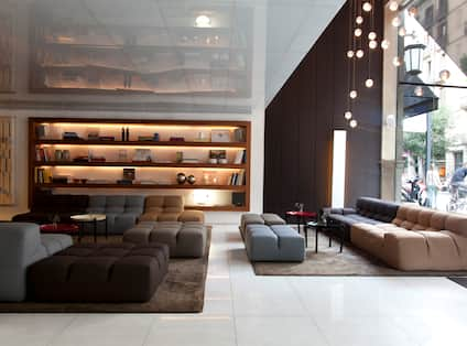 Lobby With Illuminated Shelves, Soft Seating and Decorative Lighting in Lobby Lounge Area by Large Window With View of People on the Street