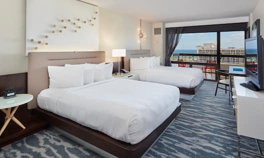 2 Queen beds in a Room with an Ocean View from the balcony , an HDTV, and a Writing Desk.
