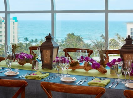 A Close Up View of the Place Settings, Lanterns, Decor and Glasses on a Banquet Table with a View Overlooking the Water