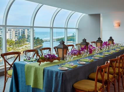 Banquet Setup in the Atlantic Ballroom with Chairs, Place Settings, and an Outside view of the Water Through Floor-to-Ceiling Windows
