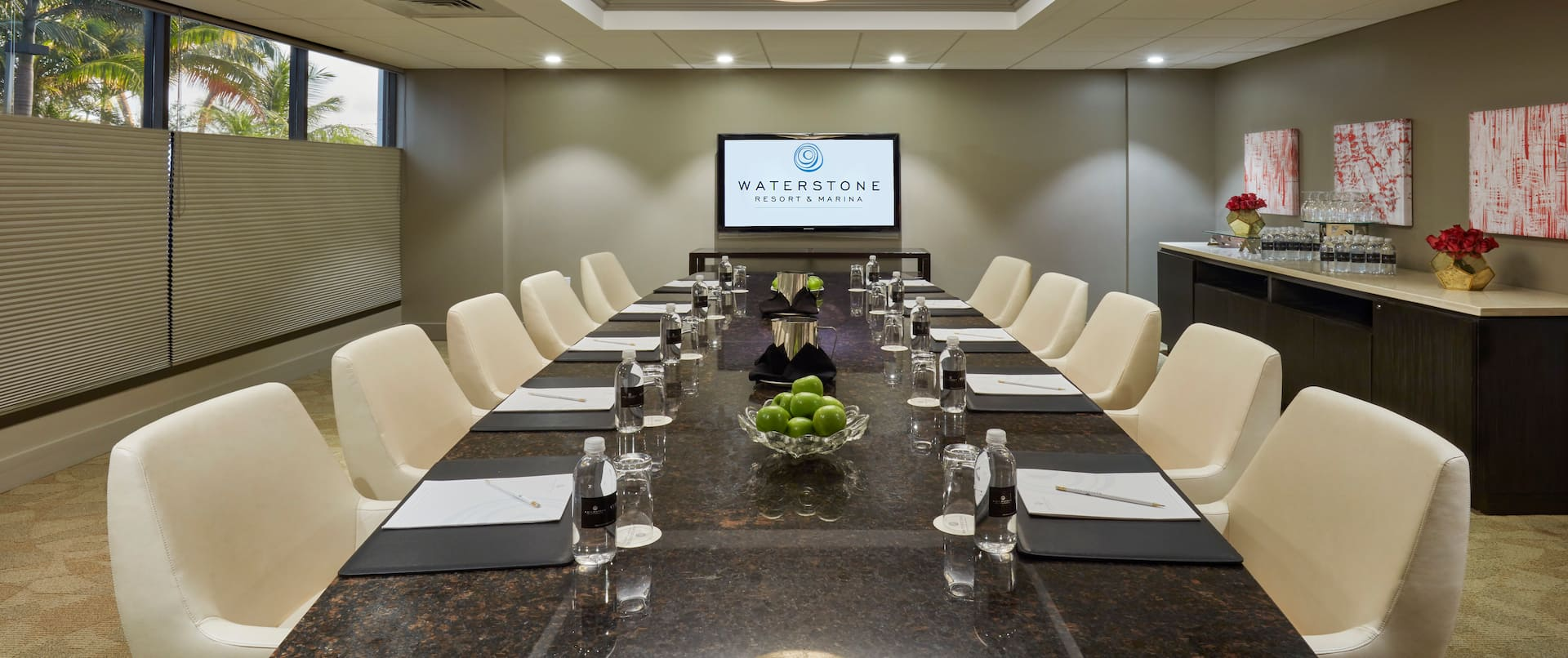 Meeting Agendas, Writing Instruments and Bottle Waters on a Long Table with  Chairs and Presentation Screen in Boardroom