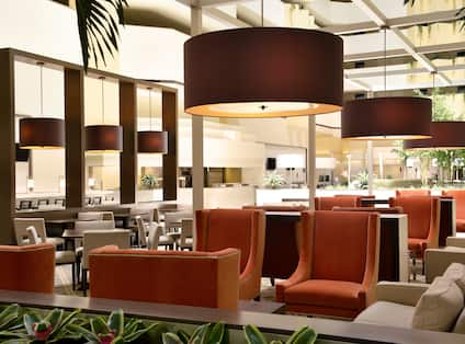 Tables, Chairs, and Soft Seating in Atrium Filled With Natural Light
