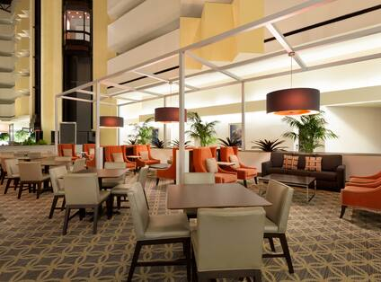 Four Chairs at Square Tables, Armchairs, Sofas, and View of Elevator Bay in Atrium