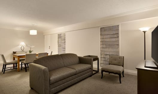 Illuminated Floor Lamp, TV, Sofa, Chair, and Seating For Six at Dining Table in Executive Suite Parlor