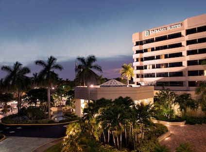 Illuminated Hotel Exterior, Signage, Palm Trees, Landscaping, and Cars on Parking Lot at Dusk