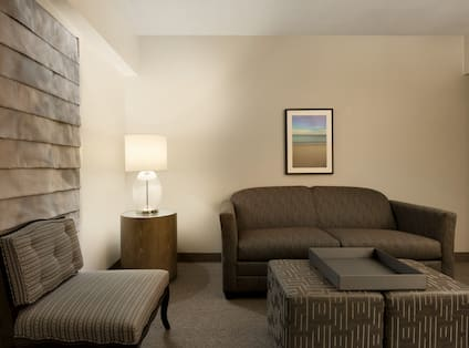 Chair, Illuminated Lamp on Side Table in Corner, Wall Art Above Soft, and Ottoman in Suite Living Room