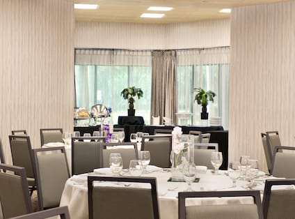 Place Settings, Drinking Glasses, and Flowers on Dining Table With White Linens, and Food Service Area by Window With Long Drapes in Bermuda Room