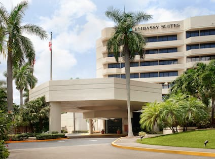 Daytime View of Hotel Exterior, Signage, Flagpole, Landscaping, and Porte Cochère