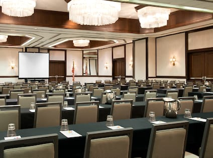Classroom Setup in Ballroom With Tables and Chairs Facing Presentation Screen and American Flag