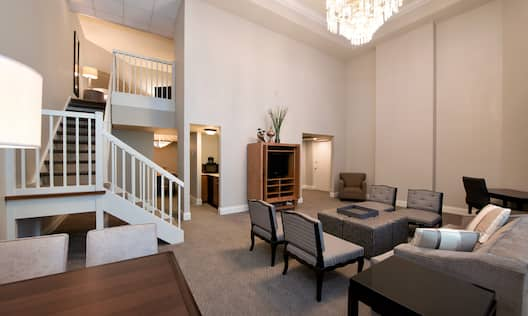 TV, Tables, Chairs, Sofa, and Staircase in Presidential Suite Living Area