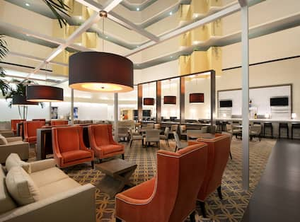 Illuminated Pendant Lights Above Soft Seating, and Tables in Atrium