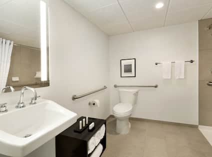 Illuminated Vanity Mirror, Sink, Fresh Towels, Wall Art Above Toilet With Grab Bars, Roll-In Shower With Grab Bars and Handheld Showerhead in Accessible Bathroom