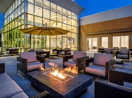 Table With Umbrella and Lounge Seating Around Patio Fire Pit at Night