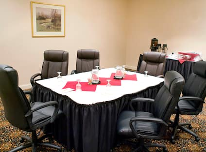 Boardroom With Wall Art, Seating for Six Around Table, and Beverage Station in Back