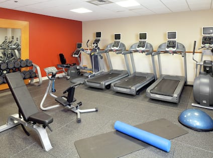 Fitness Center With Floor Mats, Weight Bench, Large Mirror, Free Weights, and Cardio Equipment