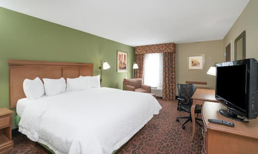 King Bed, Work Desk, Chairs, and TV in Suite