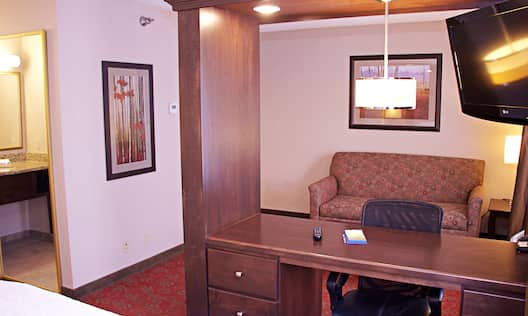 Bed in room with workdesk and couch
