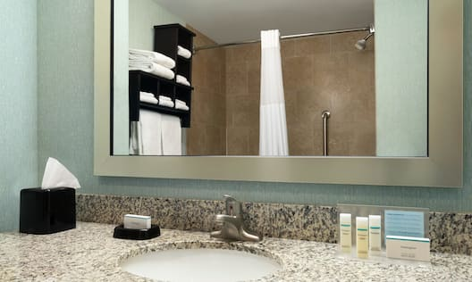 Guestroom Bathroom with Shower, Sink, and Mirror