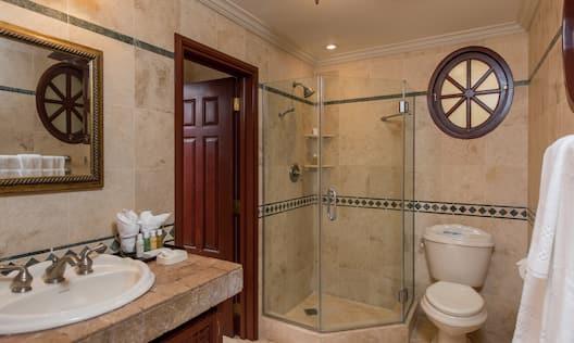 Guestroom Suite Bathroom with Mirror, Vanity, Toilet, and Walk-In Shower