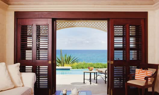 Ocean View Suite with Lounge Area and Outside View of Pool