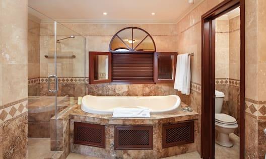 Studio Deluxe Suite Bathroom with Toilet, Jacuzzi, and Shower