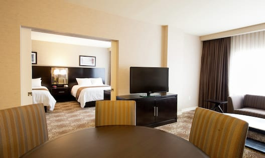 Double Queen Bed, TV, Sofa, and Dining Table in Suite