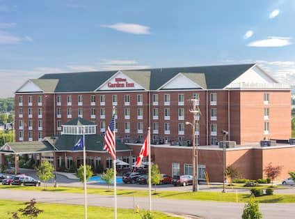 Daytime View of Hotel Exterior, Signage, Flagpole, Landscaping, Circle Drive, and Parking Lot