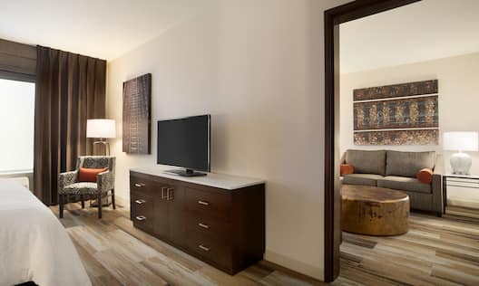 Separate Bedroom in King Suite with HDTV, Sofa, Footrest and Armchair