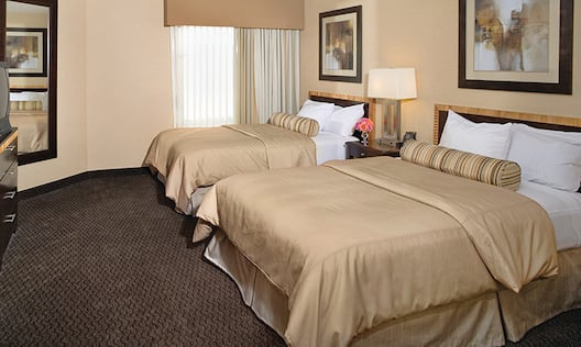 Suite bedroom with 2 double beds and tv