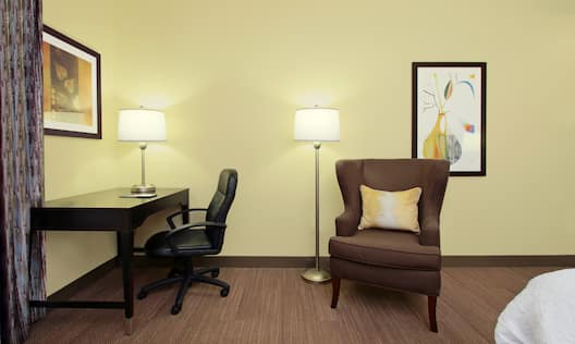 King Bed, Work Desk, Illuminated Lamps, and Armchair in Guest Room