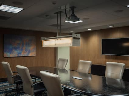 Seating for 6 Around Large Table in Private Boardroom With Wall Art and Media Screen