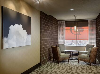 Wall Art, Four Lounge Chairs, Around Round Table in Front of Large Window With Sheer Drapes in Private Seating Area