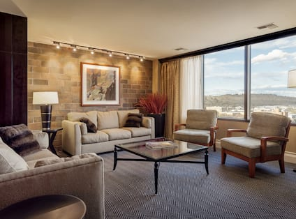 Suite Living Area With Soft Seating, Wall Art, Illuminated Lamps, Glass Table and Two Armchairs by Large Window With City View