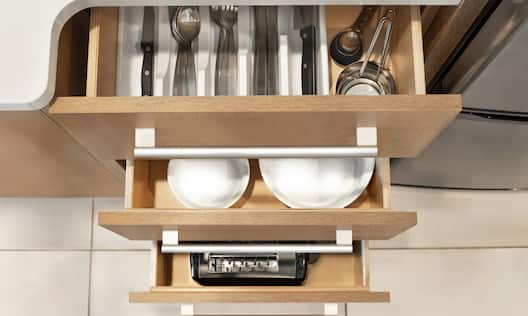 Kitchen suite dishes, utensils, measuring cups, and toaster.