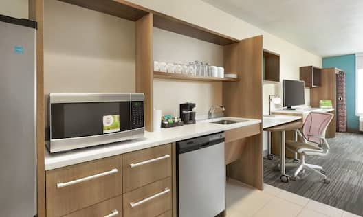 Spacious accessible suite featuring fully equipped kitchen, work desk with ergonomic chair, TV, and closet.