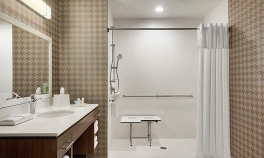 Spacious accessible bathroom featuring roll in shower with seat, mobile shower head, vanity, and large mirror.