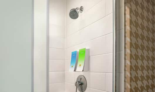Bright guestroom bathroom featuring in shower shampoo and body wash dispensers.