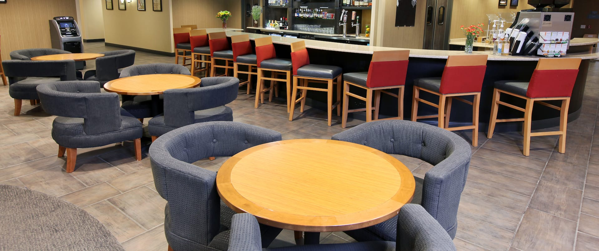 Round Tables With Blue Chairs and Red Chairs at Fully Stocked Bar of Lobby Restaurant and Lounge