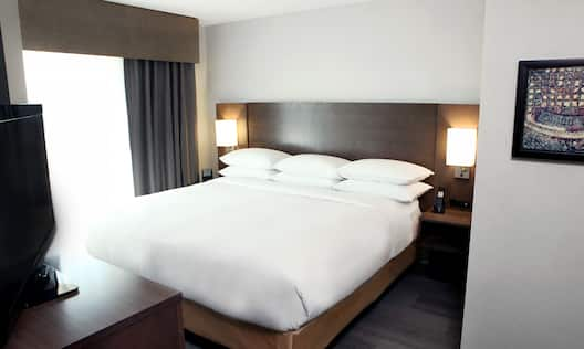 King Bed, Illuminated Lamps, Bedside Tables, Wall Art, TV and Window With Open Drapes in One Bedroom Suite