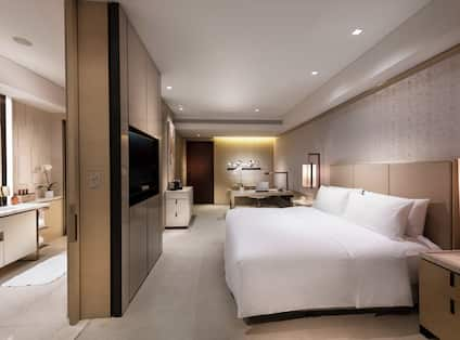 Executive King Guestroom with Bed, Work Desk, Wet Bar, and Bathroom View