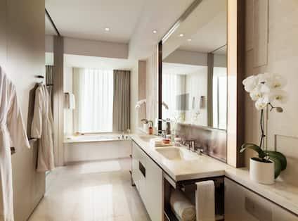 Guestroom Bathroom with Mirror, Dual Vanity, Robes, and Bathtub