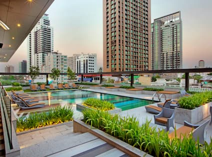 Outdoor Pool, Lounge Chairs, and City View at Sunset