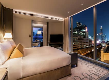 King Bed and Outside View of Illuminated City at Night in Corner Suite Bedroom