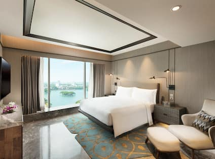 Deluxe Suite Bedroom with Armchair, Footrest, Wall Mounted HDTV and Outside View